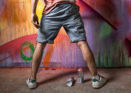 Man spraying graffiti on wall without anti graffiti coating