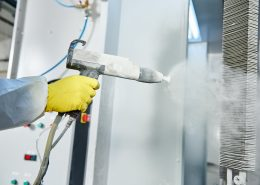Powder coating gun spraying metal object